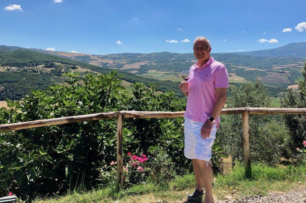 Glenn holding wine outside of Podere Le Ripi