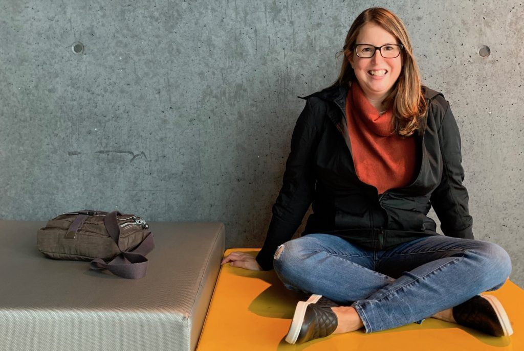 Tamara sitting on yellow bench in the Harpa concert hall