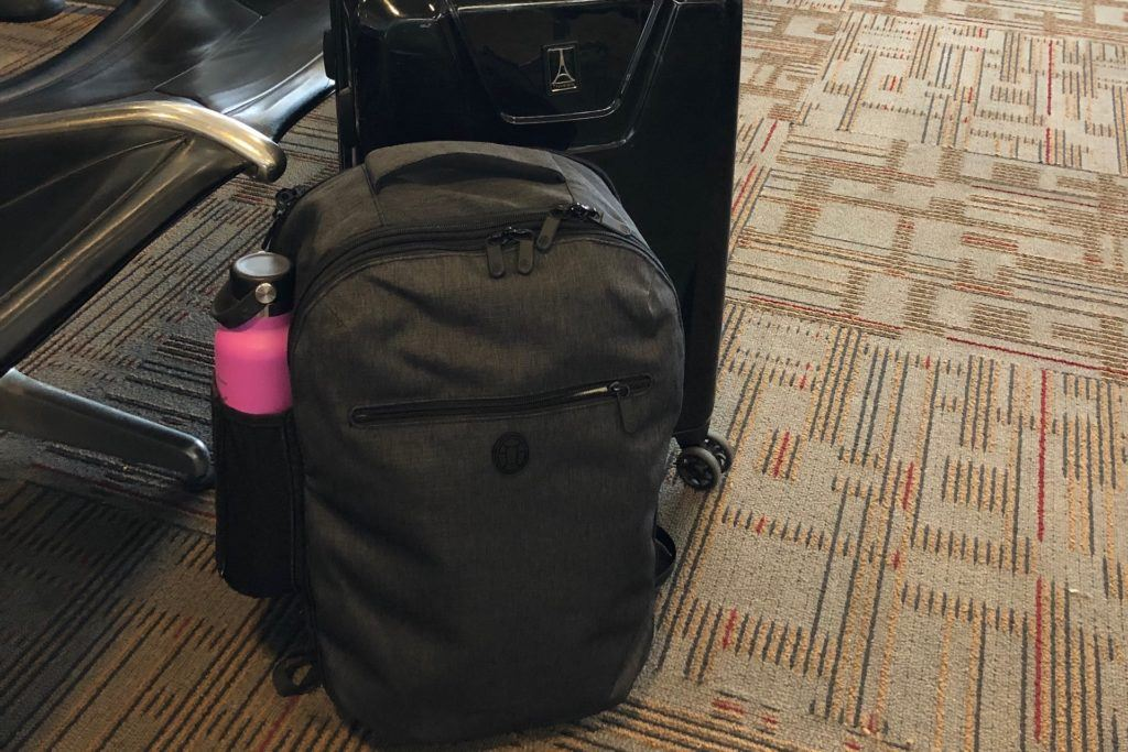 Tortuga backpack on the floor next to a suitcase