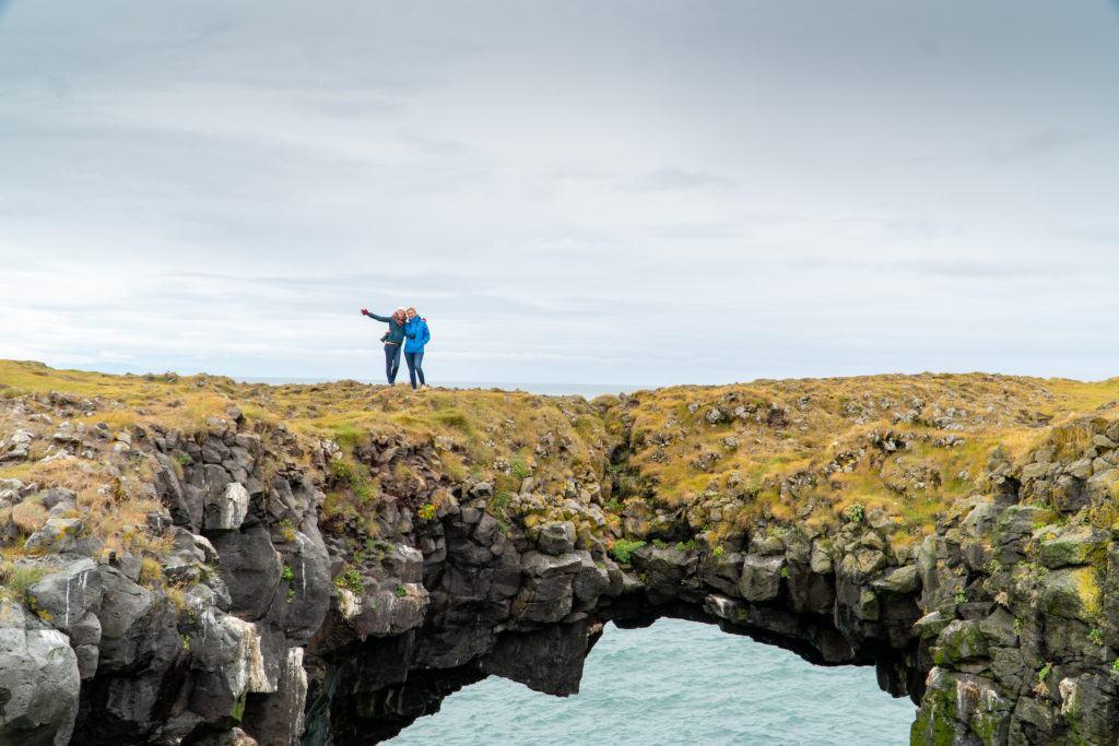Two friends standing on the Arnarstapi cliffs land bridge