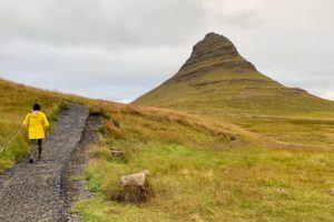 Tamara in yellow raincoat walking towards Kirkjufell mountain