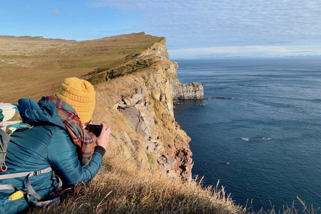 photographer leaning over Latrabarg cliffs