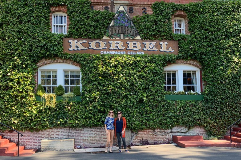 Two women in front of Korbel Champagne Cellars sign
