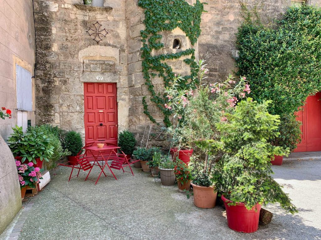 Red door in stone building surrounded by green ivy and potted plants in Pezenas France