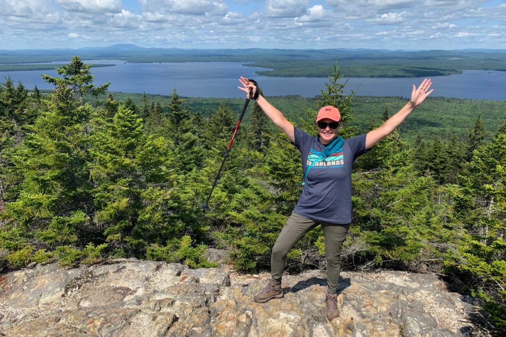 Hike with arms up holding a hiking pole at the top of Little Kineo Mountain in Maine