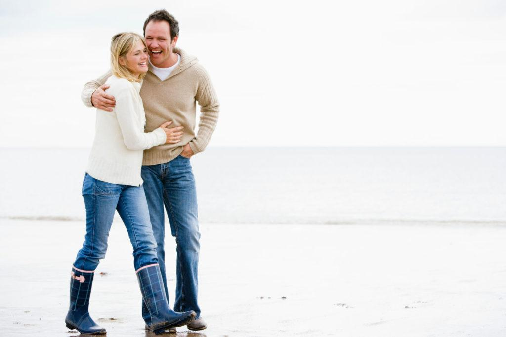 Date night ideas for married couples - Happy married couple walking on the beach