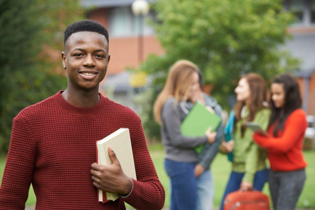 College visit black male student holding notebook with white girl students in the background