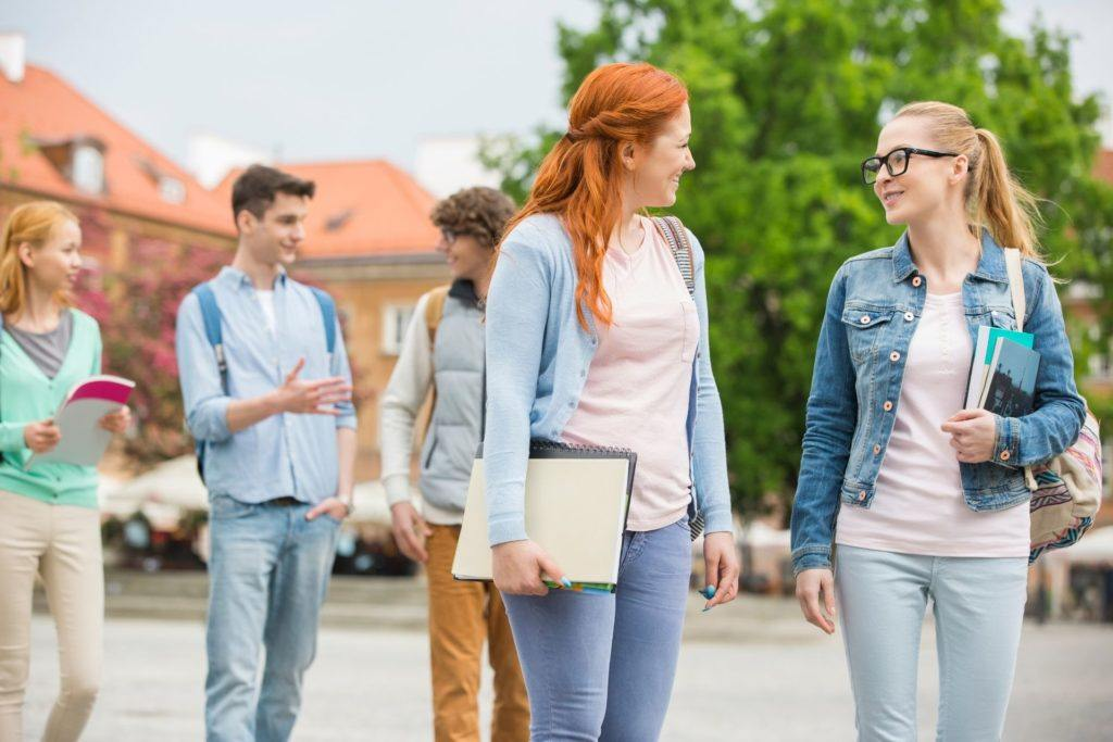 College visit white girl students in foreground, male and female students in background walking with notebooks