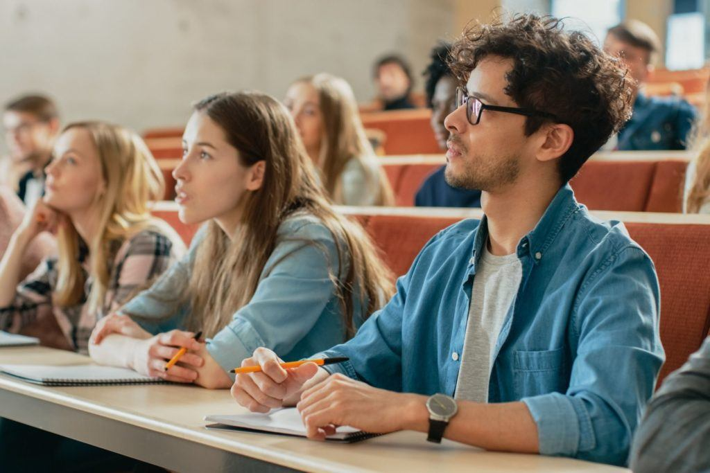 College classroom students sitting at table looking at professor
