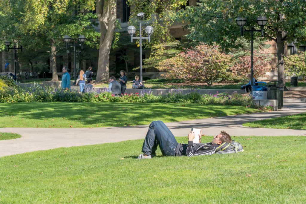 student on grass on University of Michigan campus