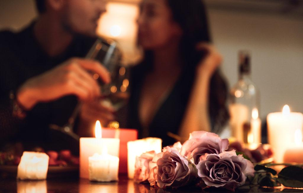 Candles, roses, couple drinking wine in background