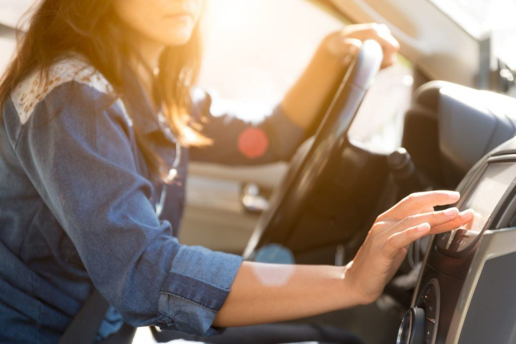 woman turning on radio in car with hand on steering wheel