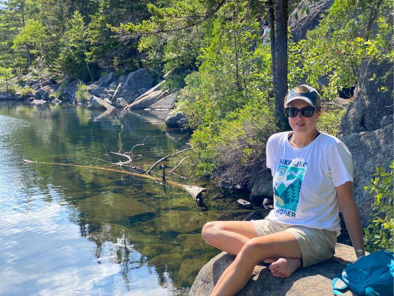 Woman sitting on rock by a pond with a Hike Like a Mother t shirt on