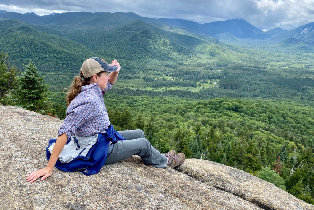 female hiker holding on to hat sitting on summit of Mt Von Hoevenberg in the Adirondacks near Lake Placid