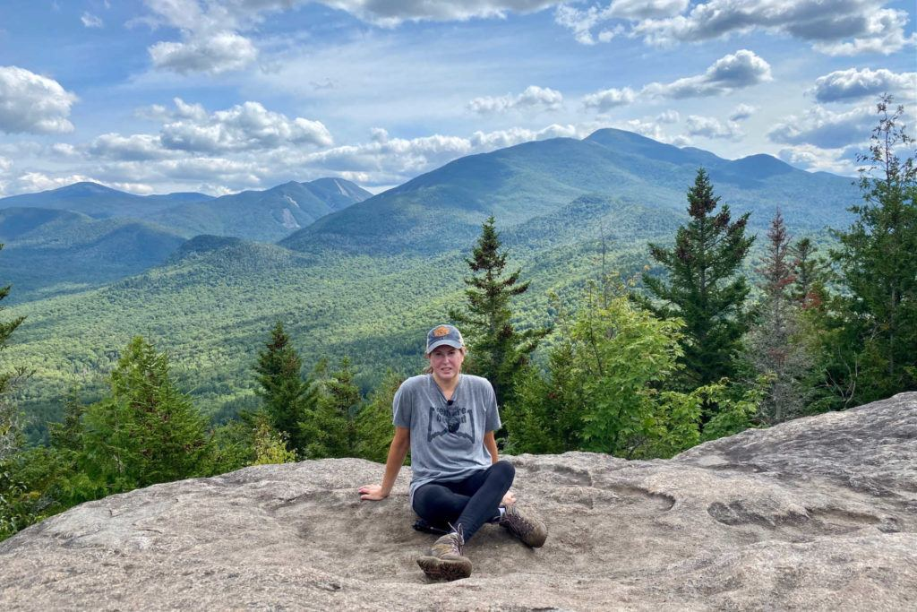 Female hiker sitting at top of Mt Jo in the Adirondacks with mountains in the background