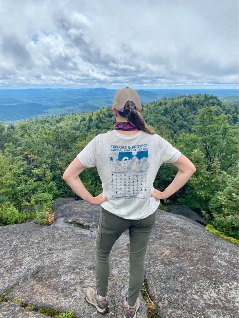 Female hiker from behind with a Parks Project t shirt on overlooking mountains