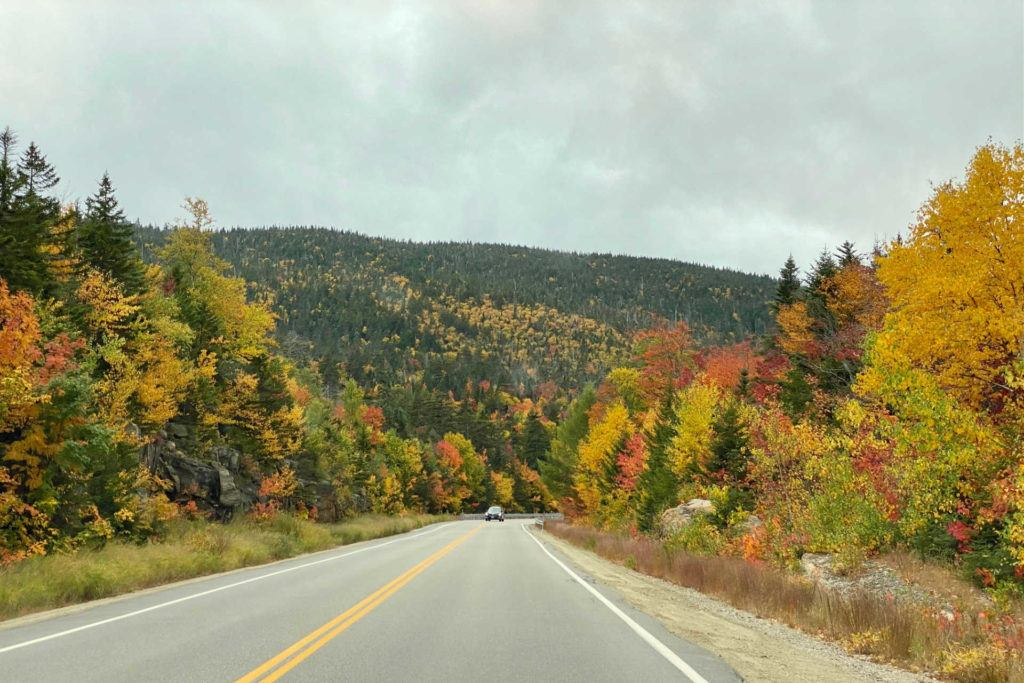 Kancamagus Highway in the fall with a car in the distance