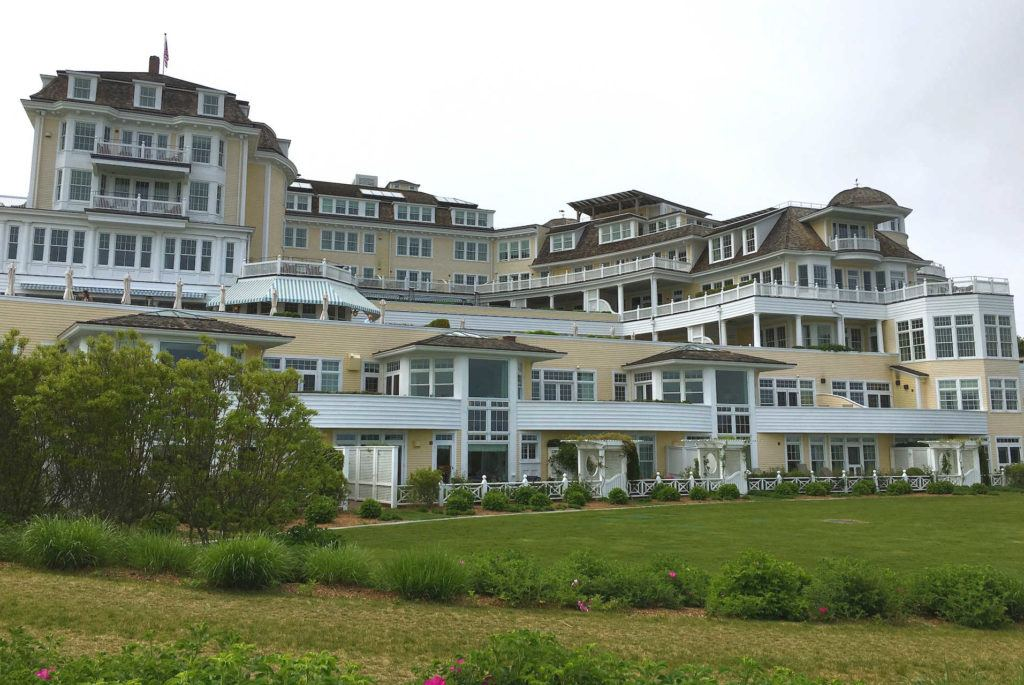 Ocean House hotel from the back with green grass lawn and yellow and white hotel