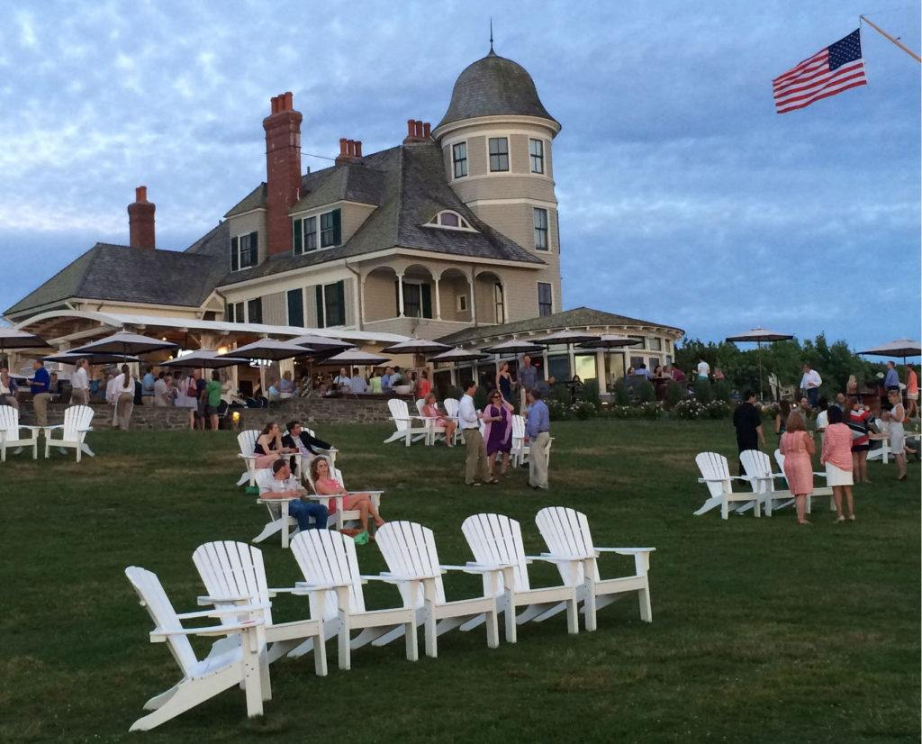 The Lawn at Castle Hill Inn in Newport with the hotel in the background and white Adirondack chairs out front