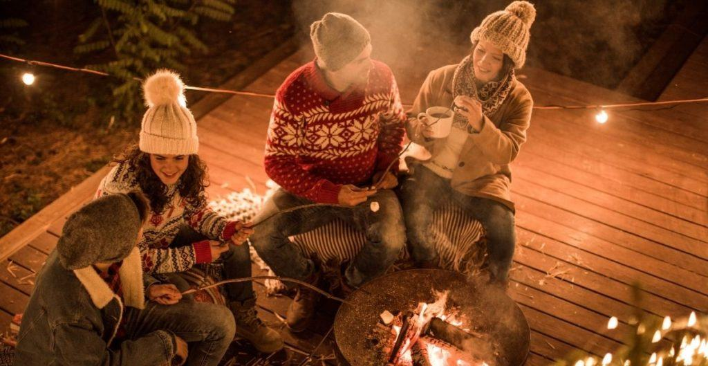 4 people sitting around a fire pit roasting marshmallows and drinking hot chocolate wearing sweaters and hats