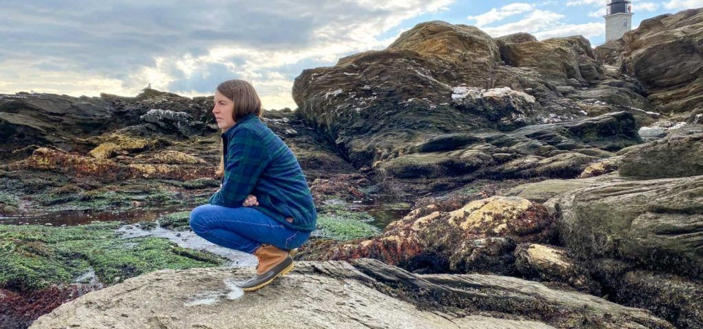 Woman in plaid shirt and LL Bean boots crouching on a rock with a lighthouse behind her