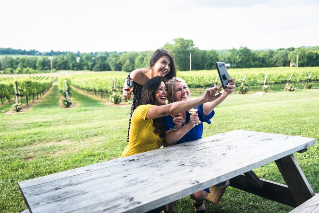 Three women holding wine at a picnic table in a vineyard taking a selfie with a phone