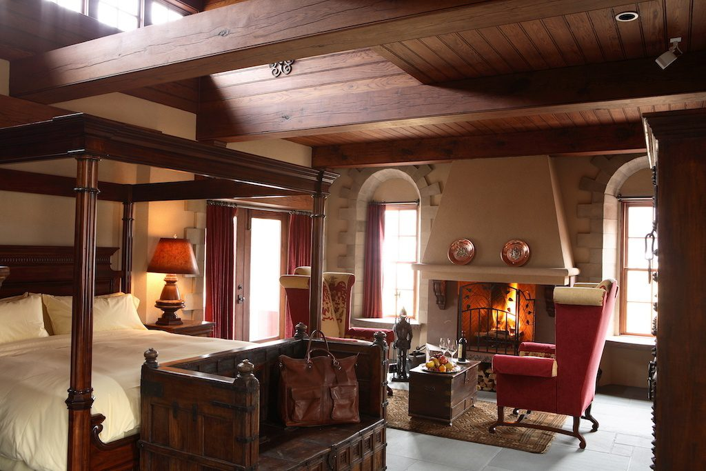Bedroom in Winvian Farm with four poster bed and fireplace with two red chairs in the front