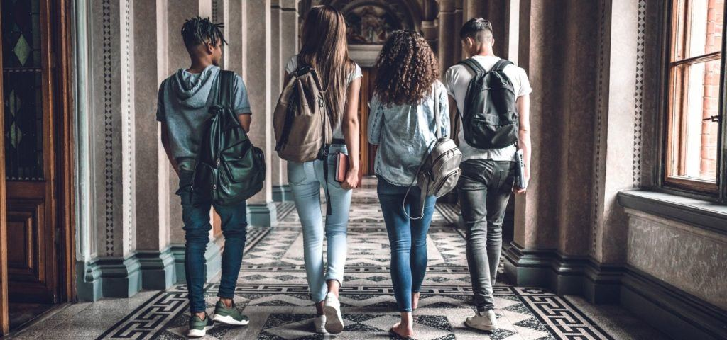 Four college students walking through hall seen from behind