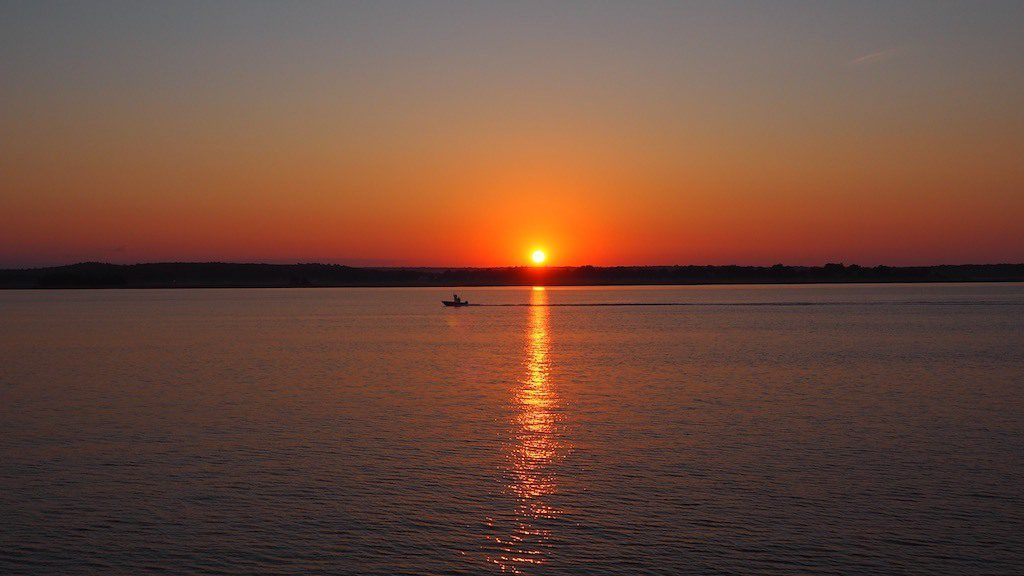 sunrise over water with a boat crossing in front of the sun peeking over the horizon