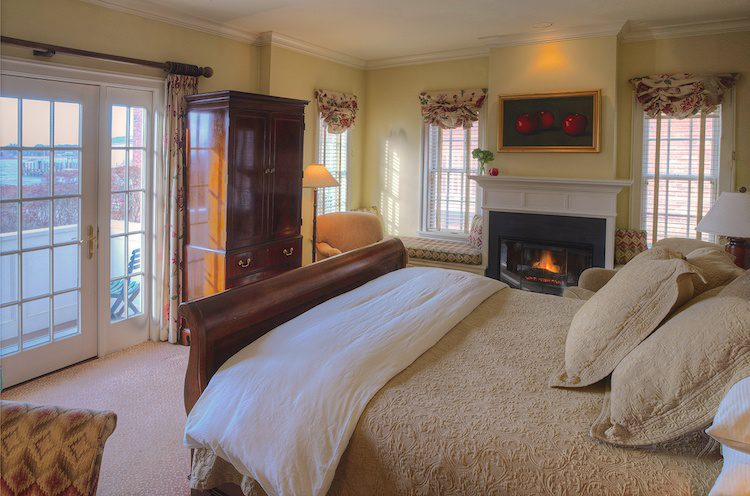 Guest room with a lit fireplace and balcony at The Inn at Stonington