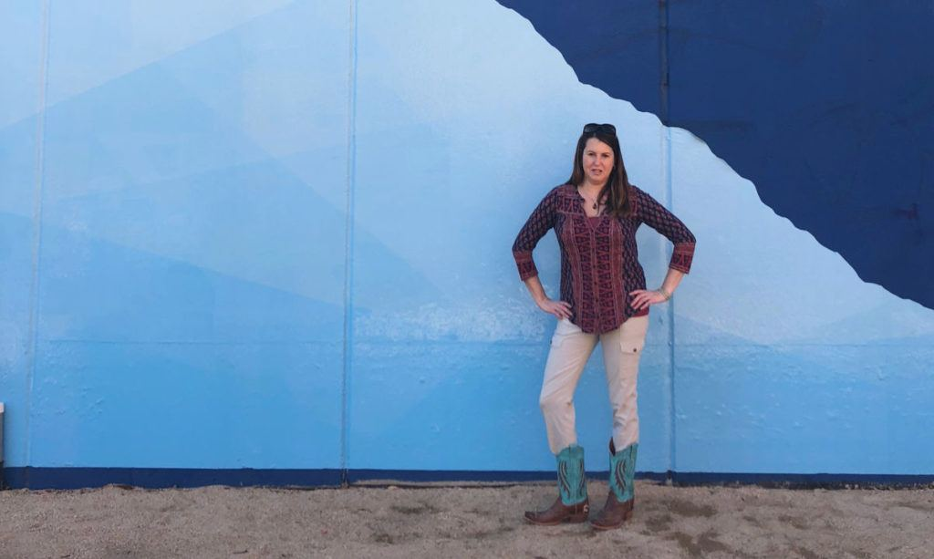 Women standing in front of blue wall with cowboy boots and hands on hips