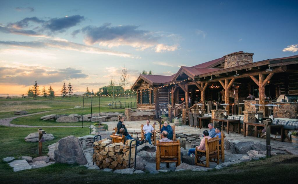 people gathered around a fire pit at sunset at Magee Homestead ranch