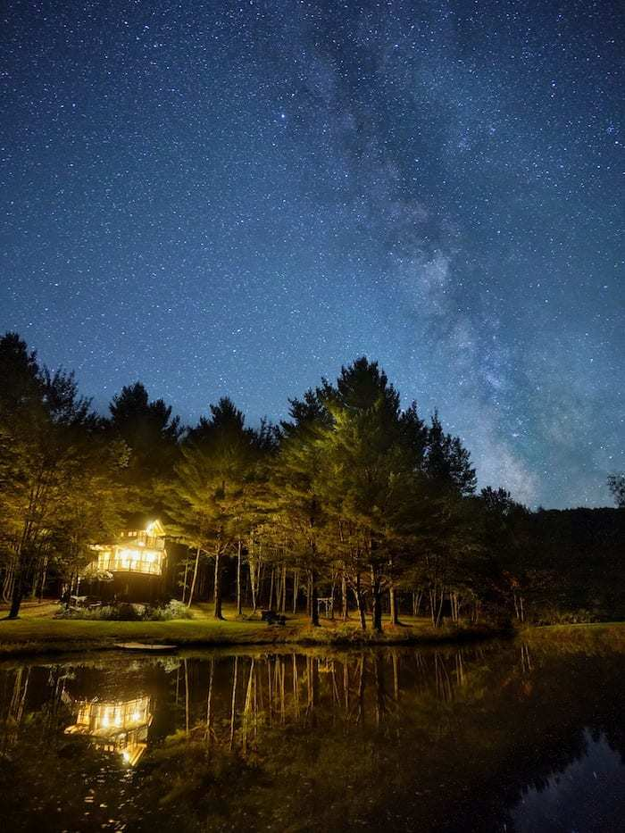 Moose Meadow Lodge treehouse reflection in lake at night with Milky Way above