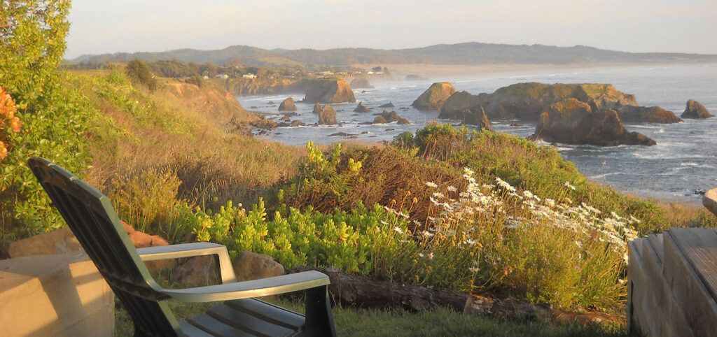 View of rocky coastline from an adirondack chair at the Inn at Newport Ranch