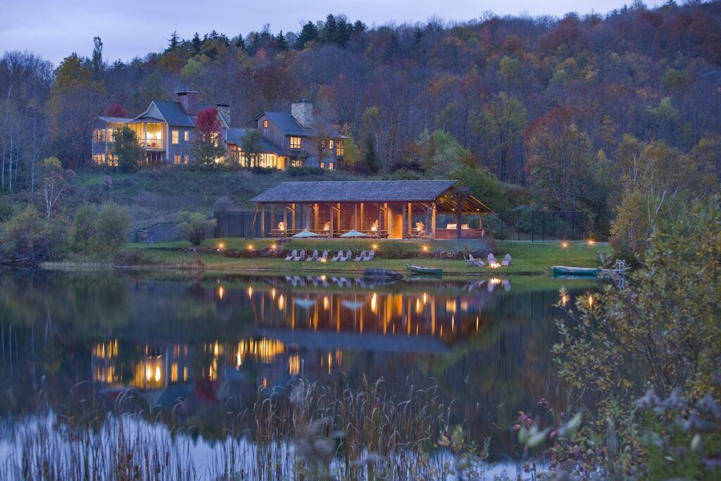 Twin Farms boathouse and lodge in the evening with lights reflecting on the water