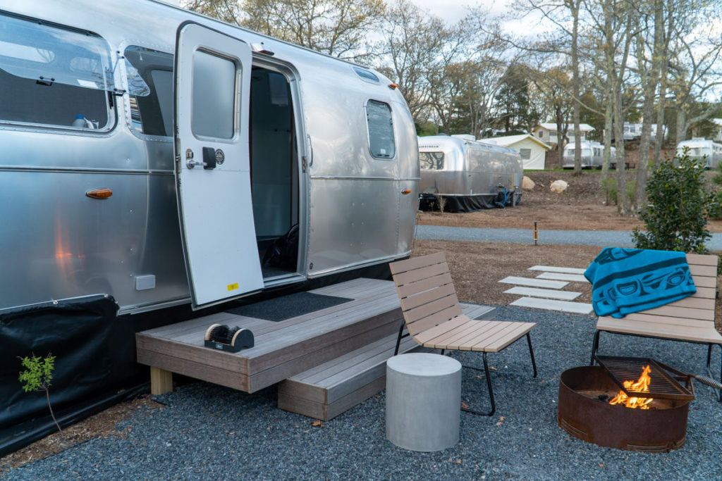 Auto Camp Cape Cod Airstream trailer with the door open and a fire lit in the fire ring outside