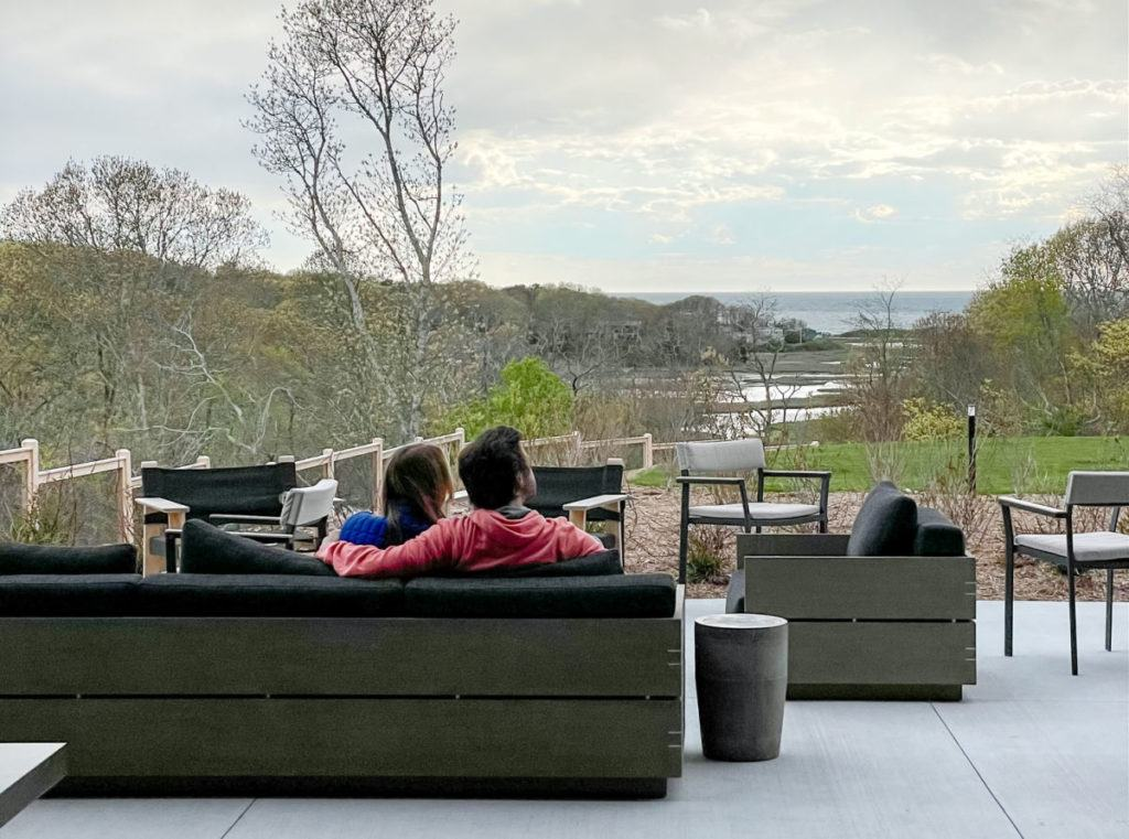 Couple sitting on sofa looking at marsh view at Auto Camp Cape Cod