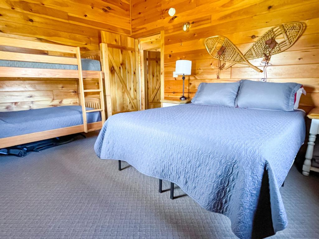 Bedroom in wood cabin with double bed and bunk beds and snow shoes on the wall