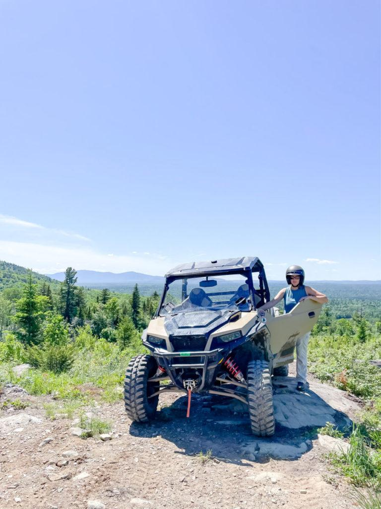 Woman in helmet standing next to a Polaris side by side on a mountain top