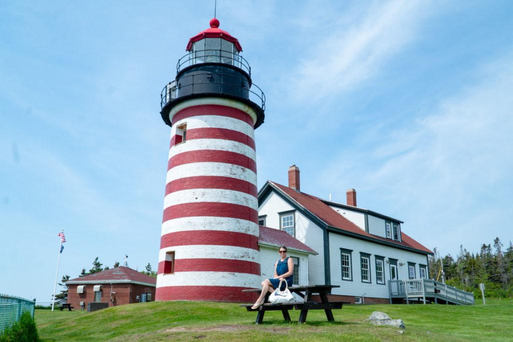 West Quoddy Head light with woman sitting on picnic table in front