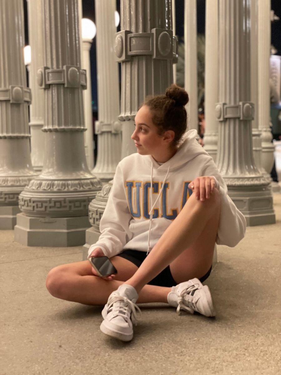 Girl in white UCLA sweatshirt sitting against white lampposts at LACMA exhibit