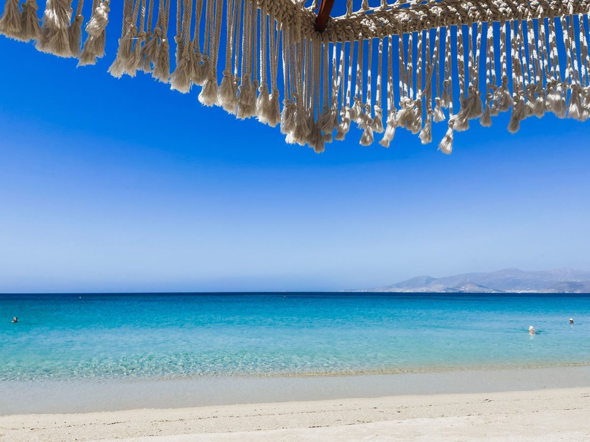 Agios Prokopios beach with blue water and white sand, looking out from under a rope umbrella at Paros in the distance