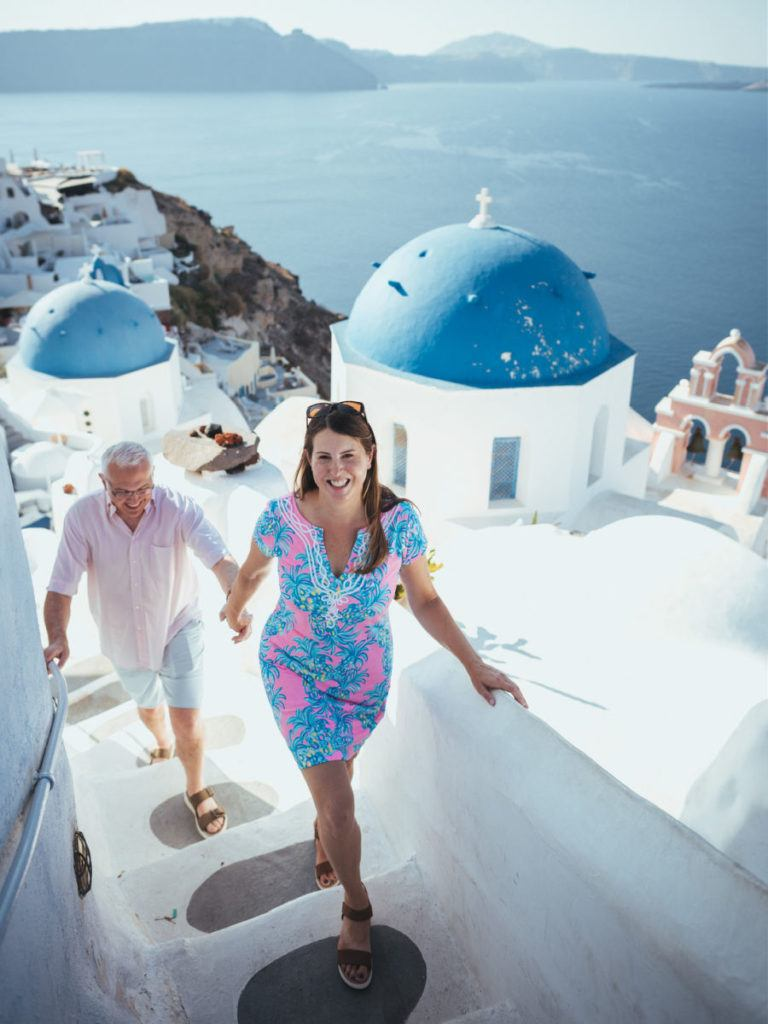 Couple walking up stairs with blue domed church in the background in Oia