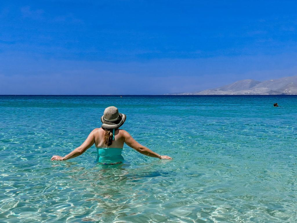 Woman with sunhat and blue bathing suit from the back standing in blue water