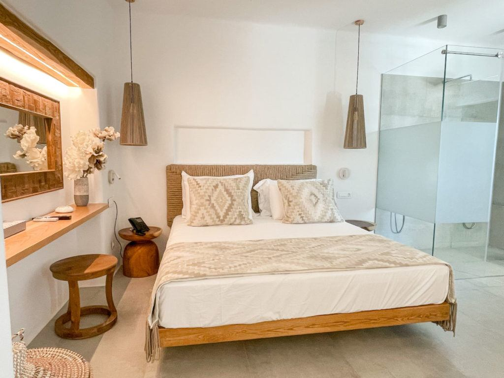 King bed and glass shower in deluxe sea view suite at the Virtu Suites