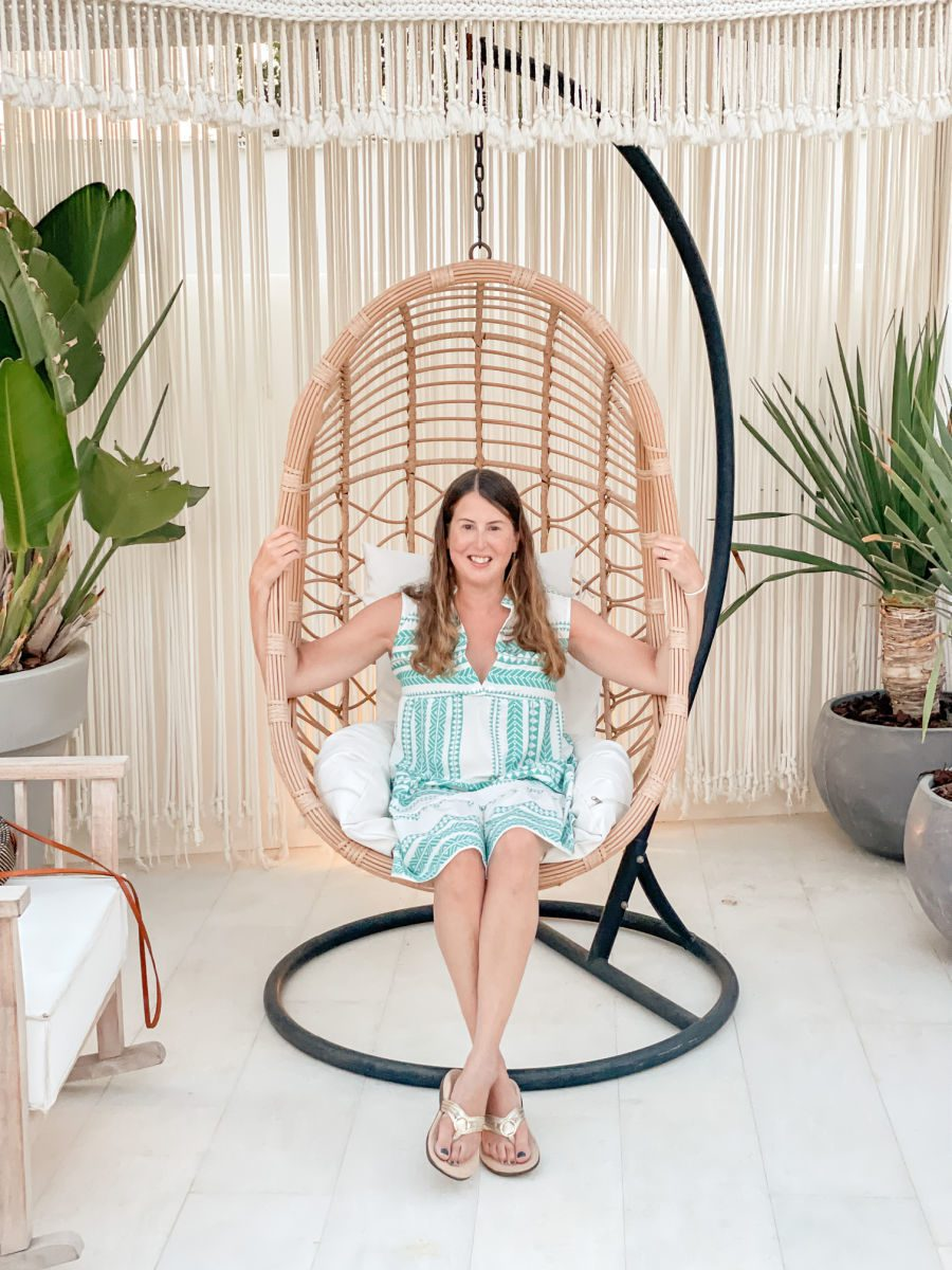 Woman in green and white dress sitting in hanging chair at Virtu Suites