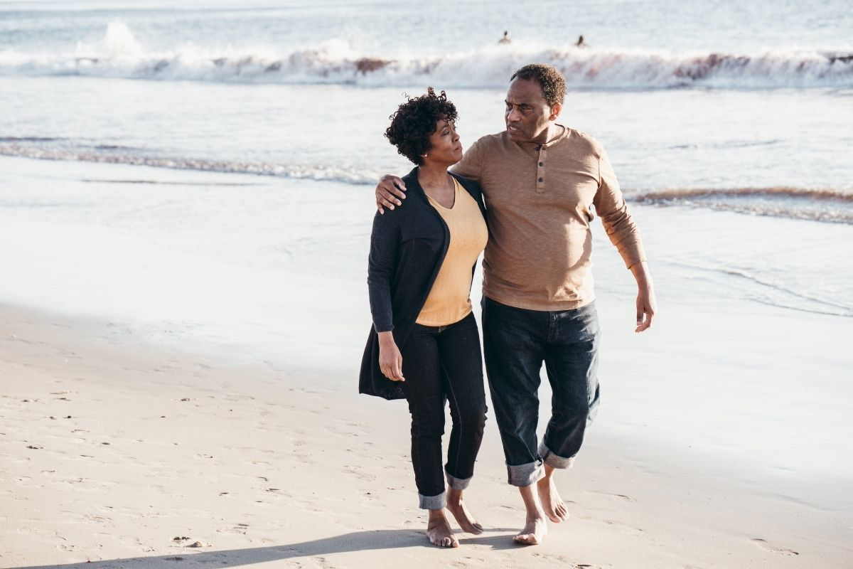 Black couple walking on the beach in California from Canva