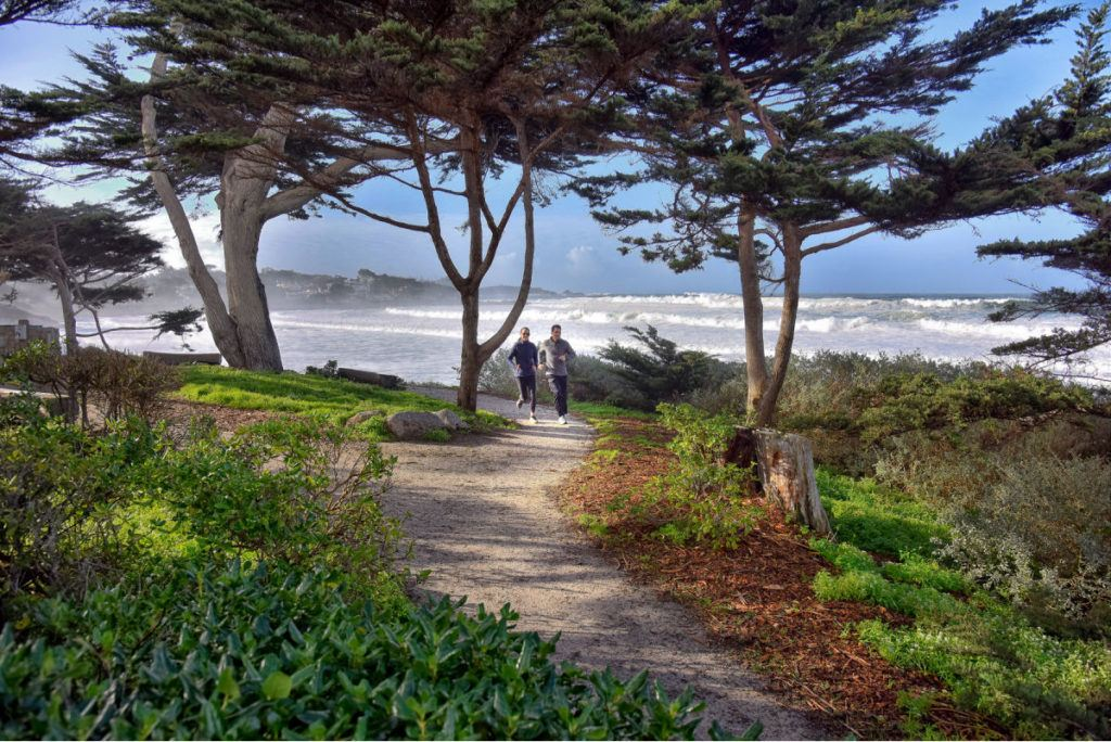 Couple running on path by ocean in Carmel by the Sea