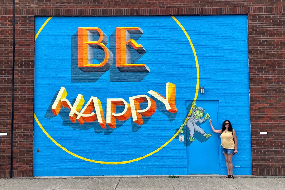 Woman in front of Be Happy mural in Buffalo