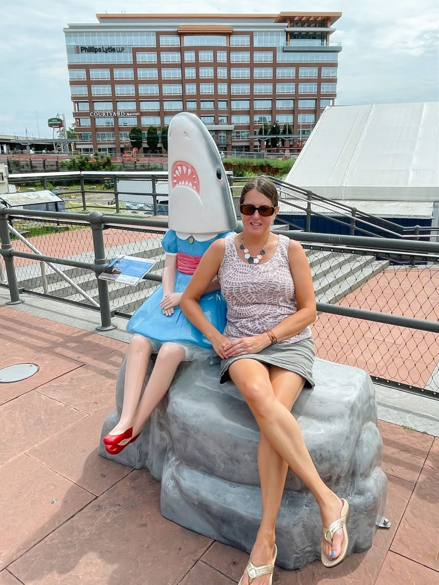 Woman sitting and leaning on Shark Girl statue